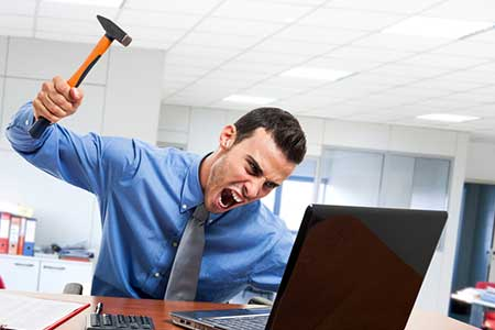 man swinging hammer at laptop